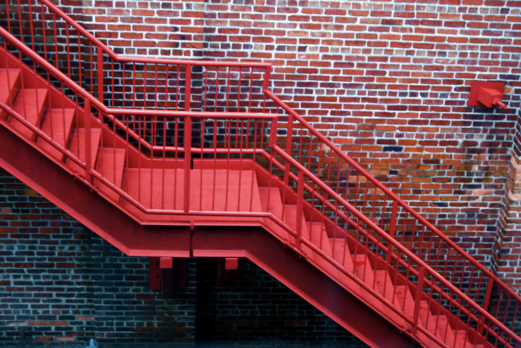 red metal staircase on a brick wall