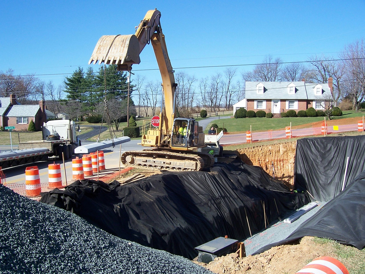 using a backhoe to dig the hole for an underground storage tank