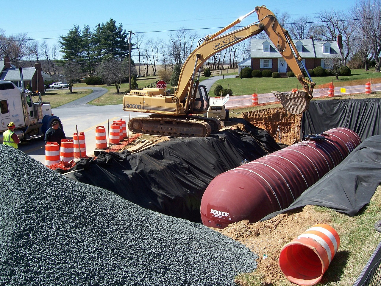 lowering an underground water tank with a backhoe